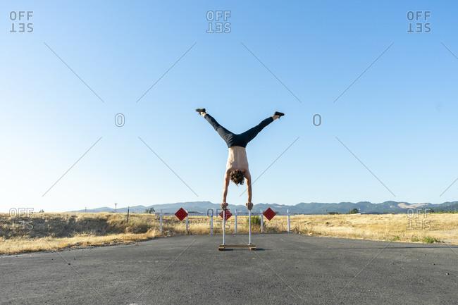 Acrobat doing handstand on handstand canes