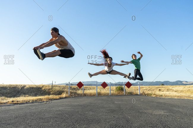 Three acrobats jumping mid-air on a dead end street