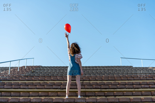 Young woman standing on grandstand- letting go of a red balloon