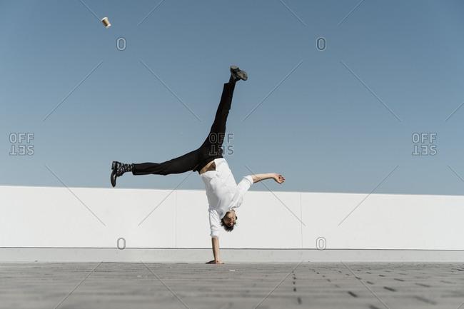 Artist doing handstand on roof terrace