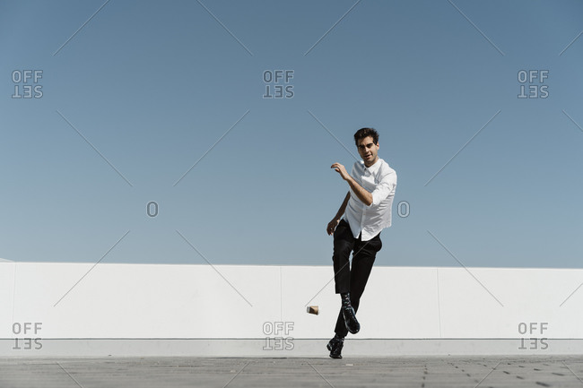 Man kicking disposable cup on roof terrace