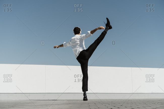 Back view of ballet dancer with headphones practicing on roof terrace