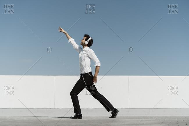 Ballet dancer with headphones practicing on roof terrace