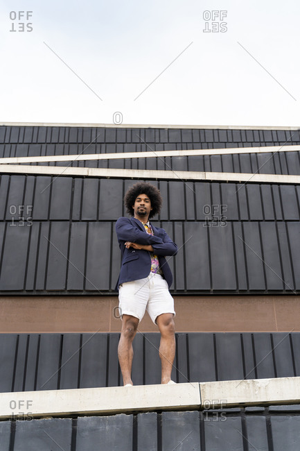 Portrait of stylish man standing on a wall