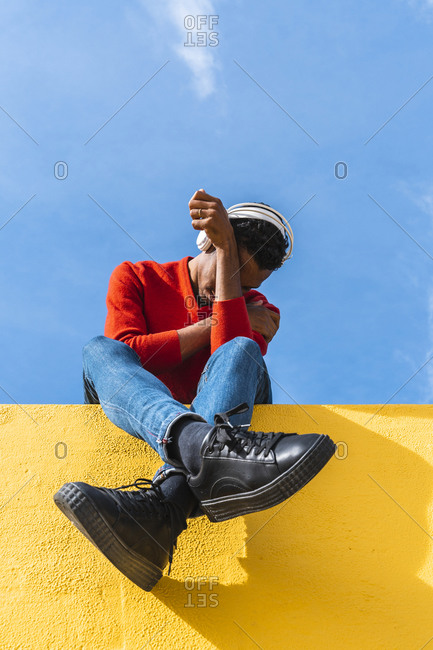Young man with headphones- sitting on yellow wall- listening music