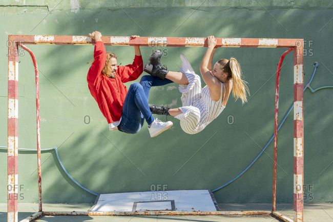 Young couple playfighting on goal posts