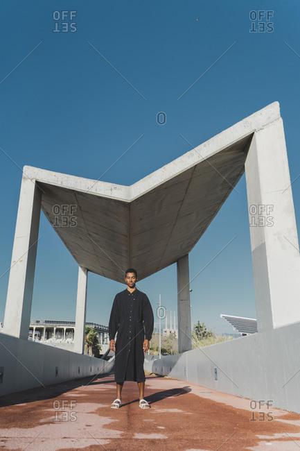 Young man wearing black kaftan standing on a footbridge