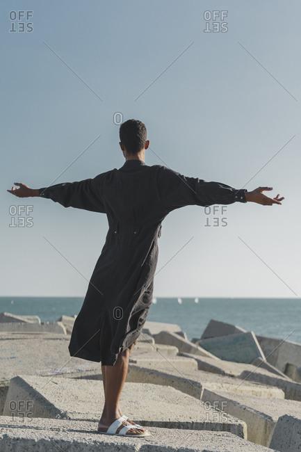 Young man wearing black kaftan on concrete blocks at the coast