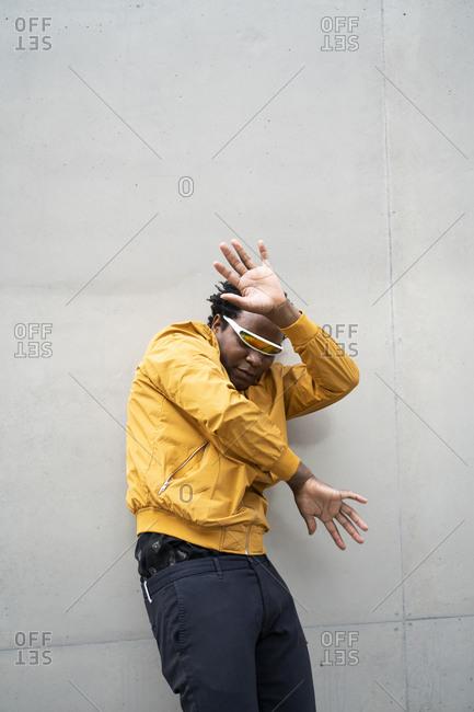 Mature man wearing mirrored sunglasses and yellow jacket raising hands