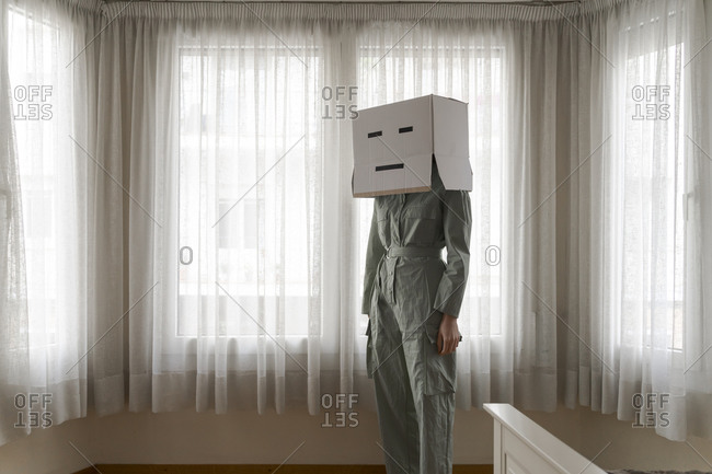 Woman wearing a card box on head with face