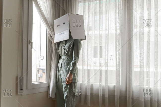 Woman wearing a card box on head with bored smiley looking out of the window