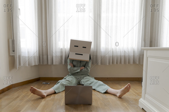 Woman wearing a card box on head with bored smiley sitting on floor and looking at laptop