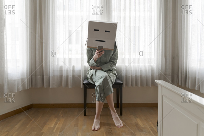 Woman wearing a card box on head with bored smiley sitting on chair and using smartphone