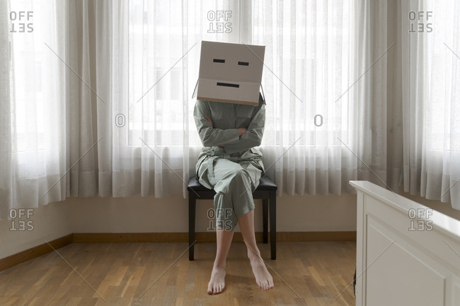 Woman wearing a card box on head with bored smiley sitting on chair with crossed arms