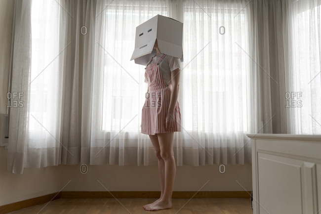 Woman wearing a card box on head with bored smiley looking out of the window at home