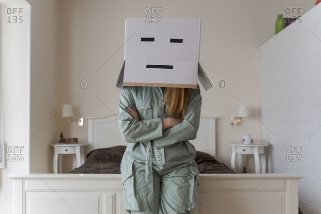 Woman wearing a card box on head with bored smiley leaning on bed at home