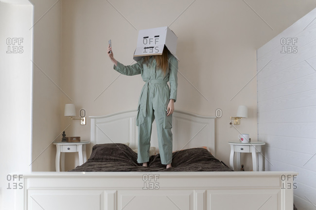 Woman wearing a card box on head with bored smiley taking a selfie on her bed