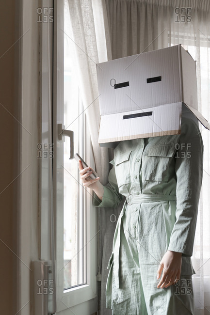 Woman wearing a card box on head with bored smiley looking out of the window and using smartphone