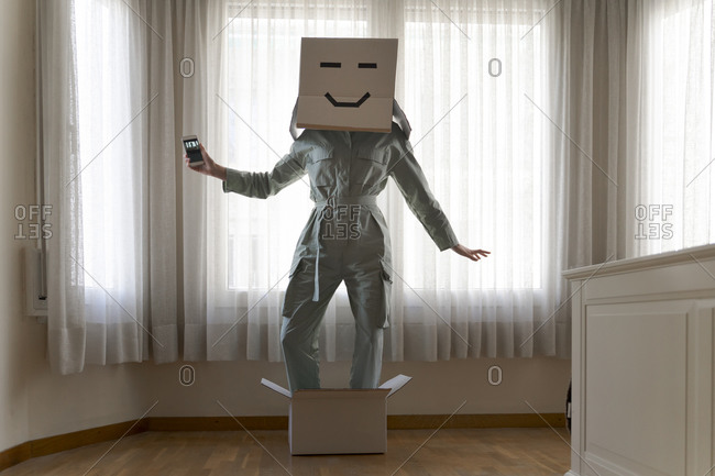 Woman wearing a card box on head with face and standing in box