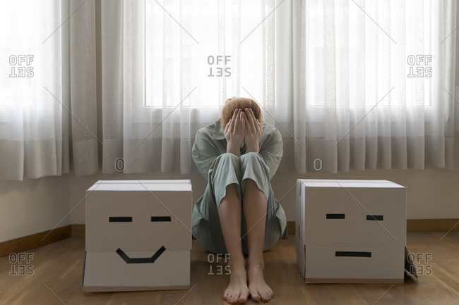Woman sitting between different card boxes at home- smiling and bored card box
