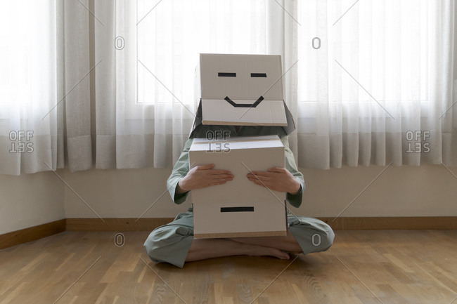 Woman wearing a card box on head with smiley face- and closing eyes of bored smiley card box