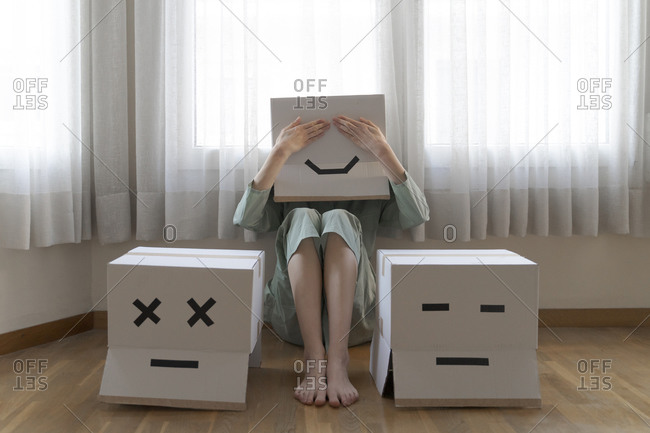 Woman wearing a card box on head with bored smiley sitting on floor in front of laptop- covering the eyes