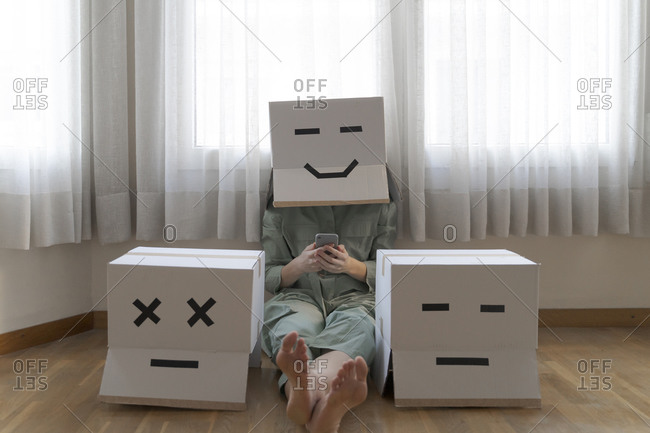 Woman wearing card box with smiling smiley and sitting between different card boxes at home and using smartphone- smiling and bored card box
