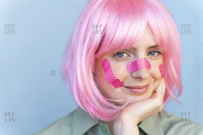Portrait of young woman wearing pink wig with plasters in her face