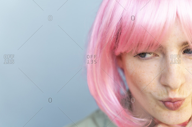 Portrait of young woman wearing pink wig pouting her mouth