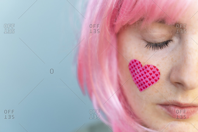 Young woman wearing pink wig with heart-shaped band-aid on her cheek