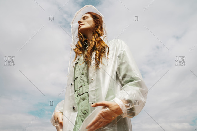 Redheaded young woman with eyes closed wearing transparent rain coat standing against sky