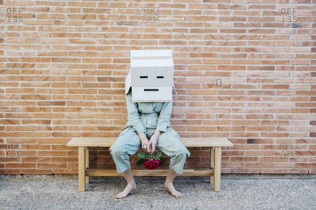 Disappointed woman sitting on bench in front of brick wall with sad face on cardboard box