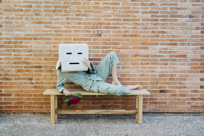 Bored woman with red rose- wearing cardboard box with sad face- lying on bench in front of brick wall