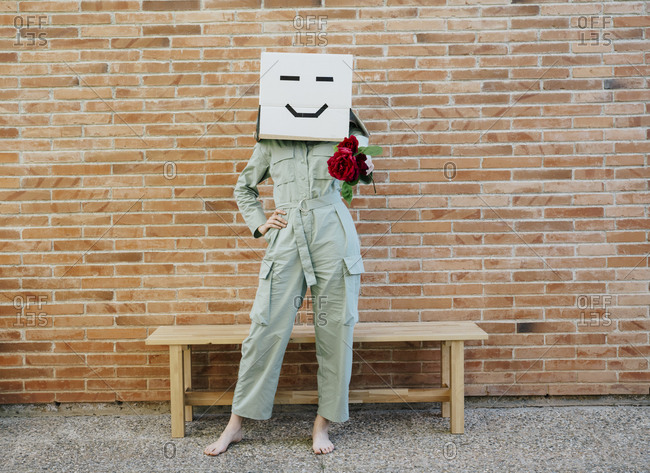Woman holding red rose- wearing cardboard box with happy face- standing by bench in front of brick wall