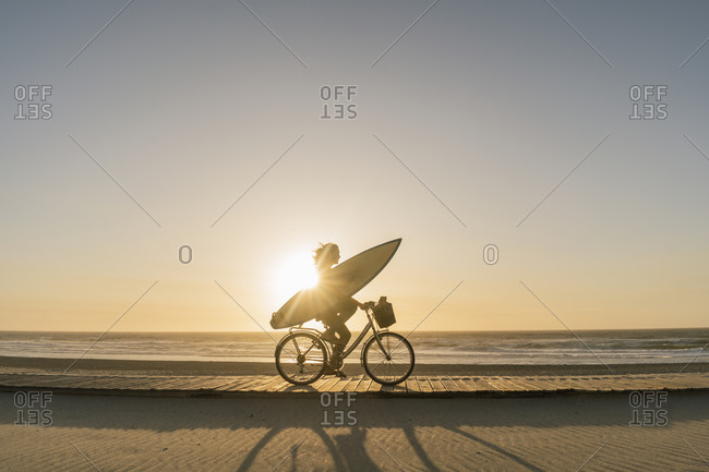 Surfer riding a bicycle during the sunset in the beach- Costa Nova- Portugal