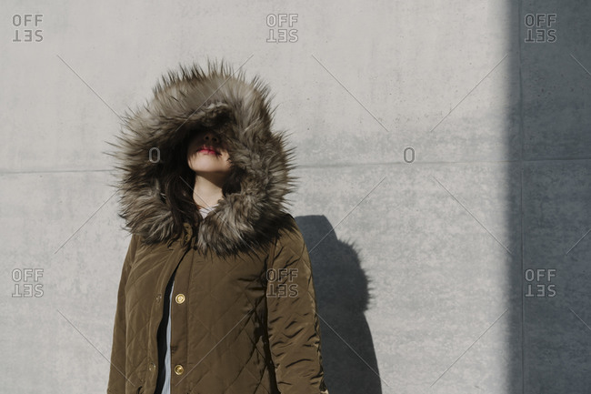 Portrait of anonymous woman with winter coat in the background of a wall