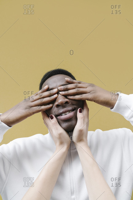 Portrait of smiling man covering eyes with his hands- touched by woman's hands