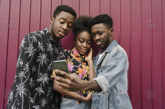 Group picture of three friends taking selfie with smartphone