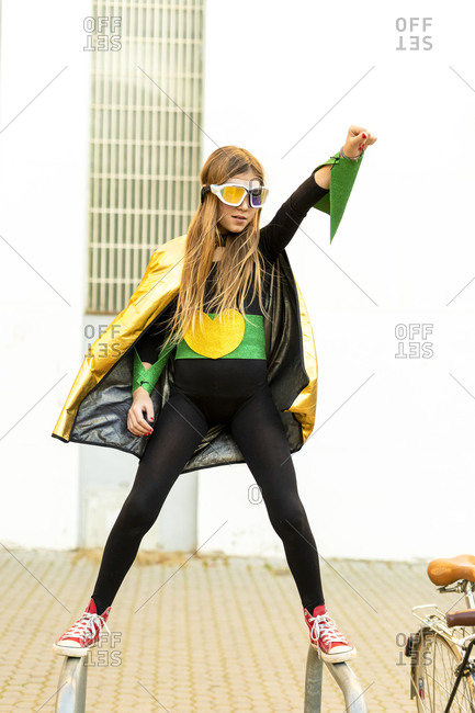 Girl posing in super heroine costume on bicycle rack