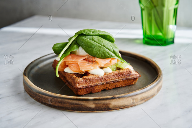 Waffle topped with sliced salmon, poached egg and spinach on light marble background