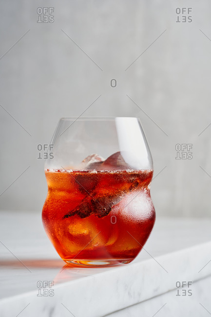 Classic Negroni served in a beautiful cocktail glass on light marble bar countertop