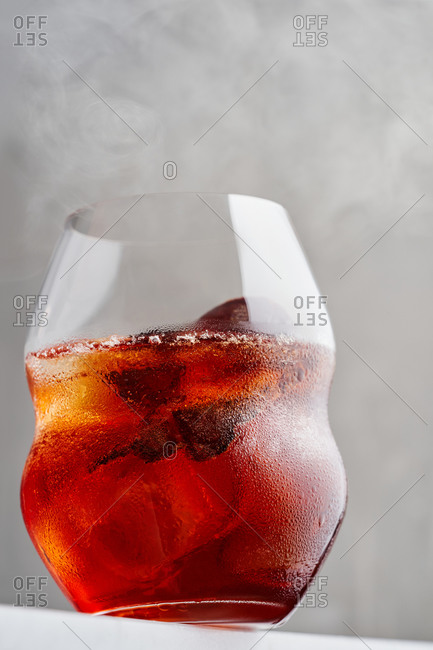 Close up view of classic Negroni cocktail served with ice cubes on bar countertop