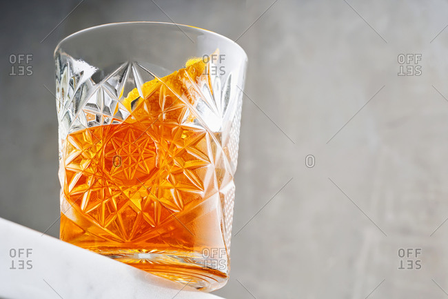 Close up view of orange cocktail in a beautiful glass on white bar countertop