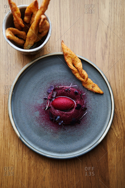 Creamy chicken liver mousse served with berry sorbet and potato bread sticks on wooden table