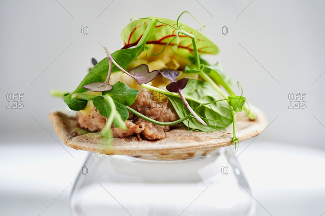 Rye flatbread with duck confit, pears and mustard sauce on white background
