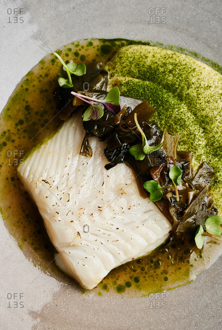 Close up view of halibut fillet served with parsnip cream, pickled wakame and sauerkraut sauce