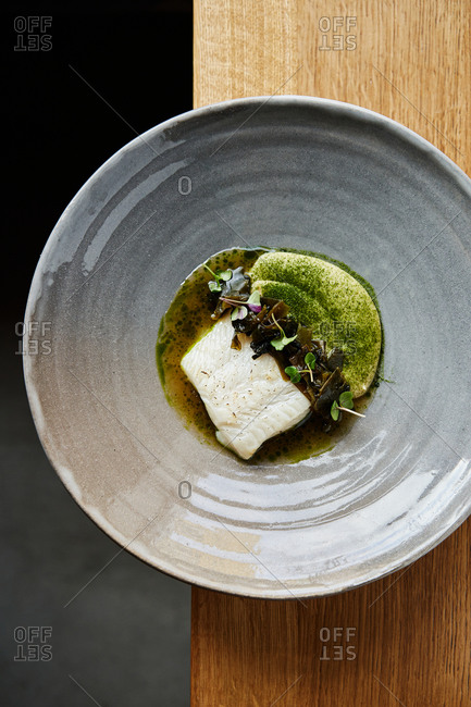 Appetizing fine dining plated main course dish of halibut filet, wakame and sauerkraut puree on wooden table