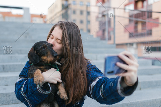 Beautiful Young adult woman taking a selfie photo kissing her dog