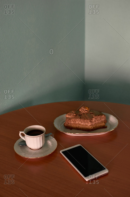 Coffee cup, a cupcake and phone on a corner table. Conceptual image