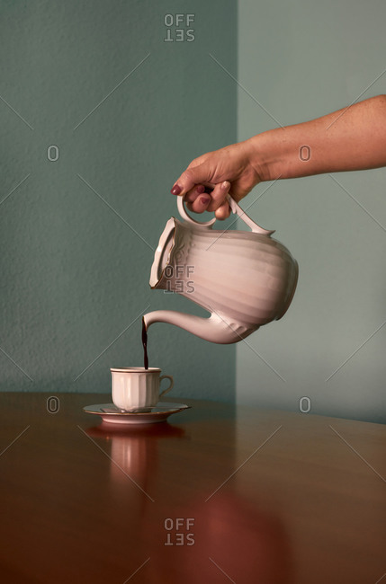 Someone pouring coffee into a cup. Conceptual image
